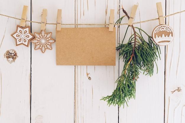 Рождественские украшения и пустой документ карты висит на фоне древесины. Premium Фотографии