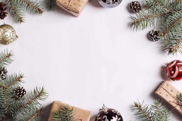 흰색 축제 테이블에 크리스마스 장식 구성 선물 상자 소나무 콘 공 가문비 나무 가지 무료 사진