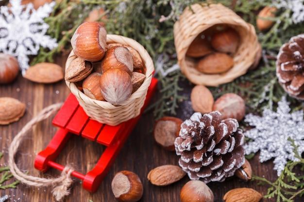 クリスマスの飾り。そりに乗ったコーン、アーモンド、ヘーゼルナッツ。 Premium写真