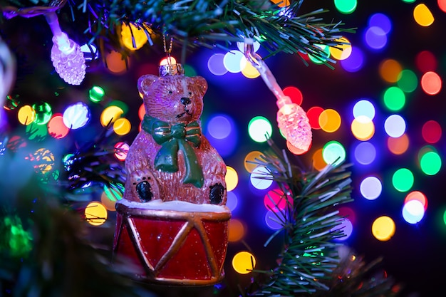 Christmas decoration in the form of a bear on a drum hanging on a christmas tree in the background many garlands in different colors glow. Premium Photo