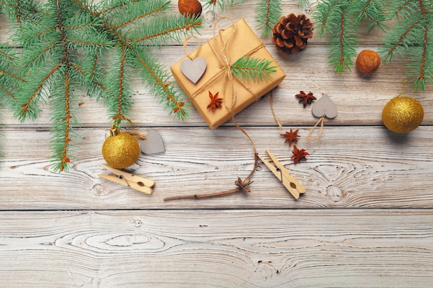 Christmas decoration, gift box and pine tree branches on wooden Premium Photo