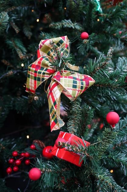 녹색 크리스마스 트리에 크리스마스 장식 소포, 리본 및 빨간 공 무료 사진
