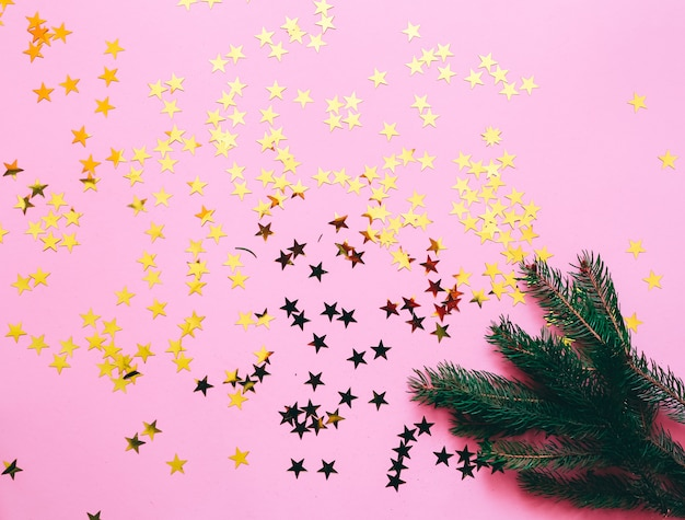 Christmas decoration on a pink background with golden stars Premium Photo