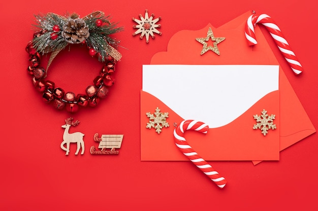 Christmas decoration on a red background and consisting of a red envelope with an empty white letterhead inside for text and decorated with christmas candies and a new year's wreath Premium Photo