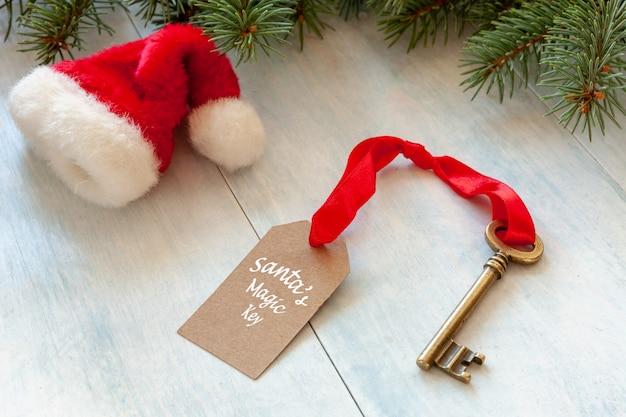 Christmas decoration - santa's magic key and santaã¢â€â™s hat. close-up on light blue back Premium Photo