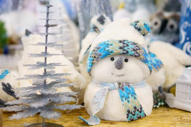 Pupazzo di neve bianco giocattolo decorazione natalizia fatto di cotone idrofilo con una sciarpa blu, sullo scaffale del negozio Foto Gratuite