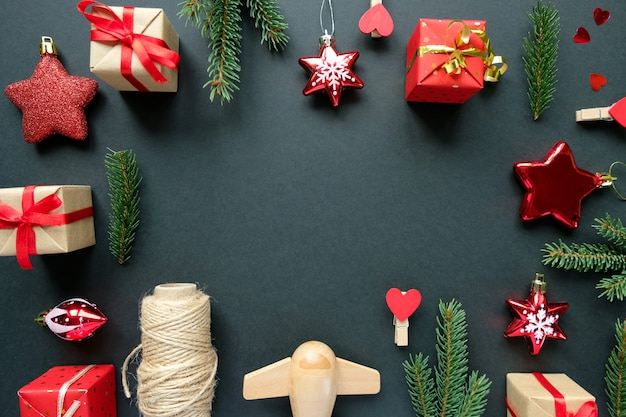 Christmas decoration with branches, stars and gift boxes on black frame background Premium Photo