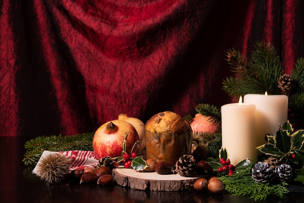 Decorazione natalizia con candele ramo di pino coni frutti e panettone Foto Gratuite