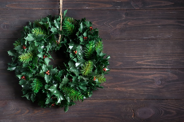 Christmas decoration wreath of green leaves and berries holly ilex plant isolated on dark wooden . copyspace Premium Photo