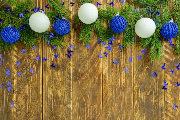 Christmas decorations, blue and white balls on a brown wooden table. top view, copy space. Premium Photo