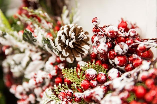 クリスマスの飾り。赤い果実と雪と新年の木の枝 Premium写真