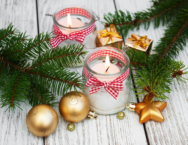 Christmas decorations candles in glass jars with fir Premium Photo