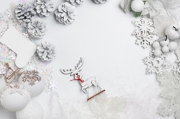 白いテーブルの背景におもちゃのクリスマスの装飾的な構成。 無料写真
