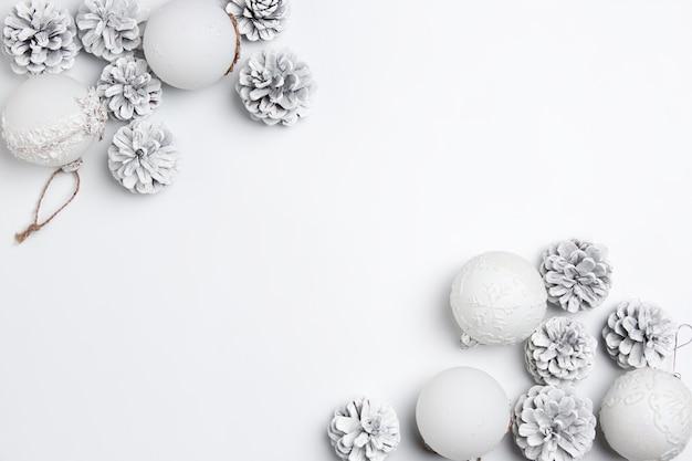 白い壁のシュルレアリスムのおもちゃのクリスマスの装飾的な構成。上面図 無料写真