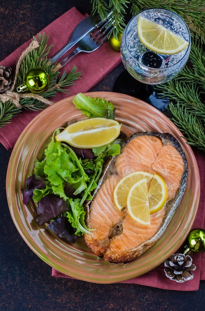 Christmas dinner table setting. delicious salmon steak grilled on plate with lemon and assorted salad on dark stone table . top view, copy space Premium Photo