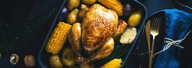 Christmas dinner table with chicken on dark Free Photo