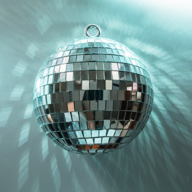 Christmas disco ball with rays on neon blue. Premium Photo