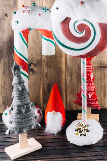 Christmas elf with big candies on table Free Photo