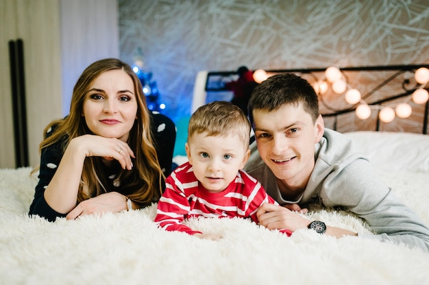 Рождественская семья! счастливая мама, папа и маленький сын в свитерах санта-клауса, лежа. смотрим любовные объятия, праздники людей. с рождеством Premium Фотографии