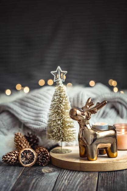 Рождественский праздничный фон с игрушечным оленем, размытый фон с золотыми огнями и свечами Бесплатные Фотографии