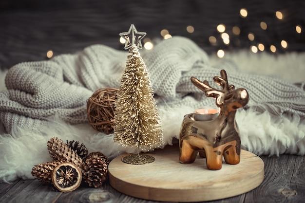 Рождественский праздничный фон с игрушечным оленем с подарочной коробкой, размытый фон с золотыми огнями Бесплатные Фотографии