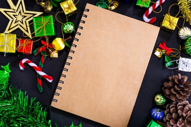 Christmas festive decorations with empty notebook and pencil on black paper background, ne Premium Photo