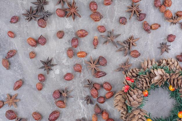 大理石の背景に松ぼっくりとスターアニスのクリスマスのお祝いの花輪。 無料写真