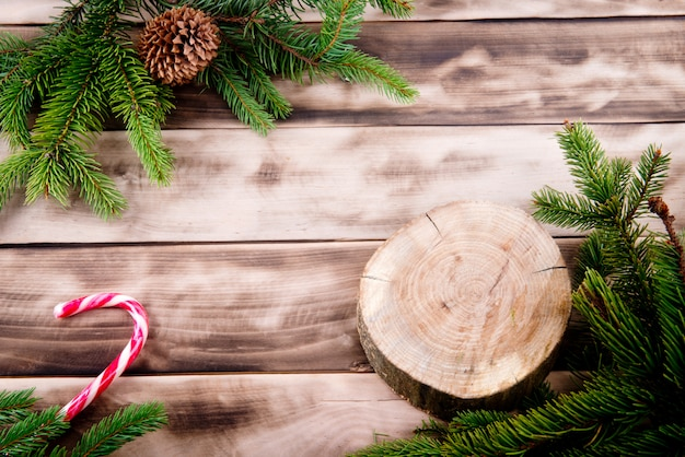 Christmas fir tree on natural wood with candy and round wooden cut. Premium Photo