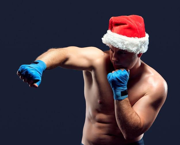 Рождественский фитнес-боксер в шляпе санта-клауса на черном Бесплатные Фотографии
