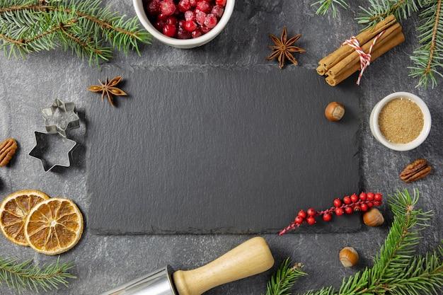 크리스마스 플랫 겨울 향신료와 어두운 배경에 제빵 재료 누워. 프리미엄 사진