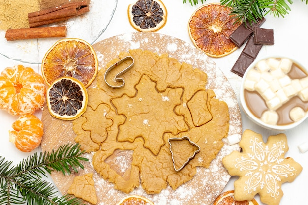 Christmas food. homemade gingerbread cookies with ingredients for christmas baking and kitchen utensils on a white table Premium Photo