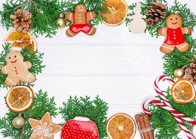 モミの木の枝、乾燥したオレンジ色のリング、クッキーのクリスマスフレーム Premium写真
