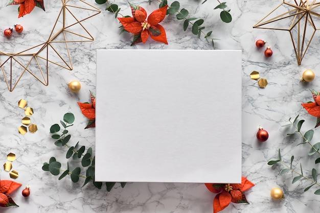 新鮮なユーカリの小枝、赤いポインセチアの花、幾何学的な装飾-六角形、金属線の形のクリスマスフレーム。トレンディなフラット横たわっていた、大理石の背景にトップビュー。白いキャンバスにコピースペース。 Premium写真