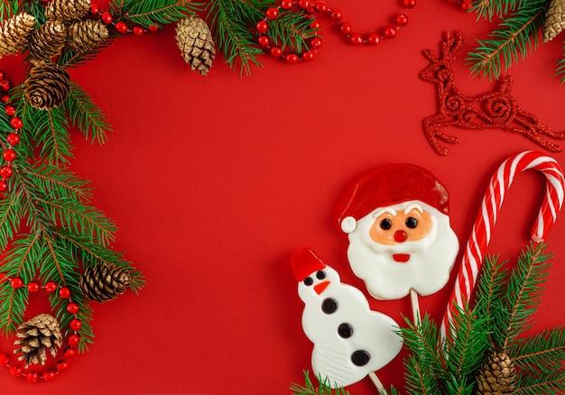Новогодняя рамка с традиционными конфетами, мехом и шишками на красном Premium Фотографии