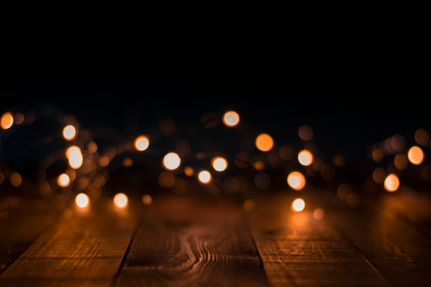 Christmas garland lights blurred on wooden Premium Photo