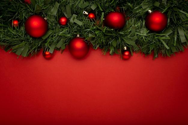 빨간색 테이블에 나뭇잎과 공으로 만든 크리스마스 화 환 무료 사진