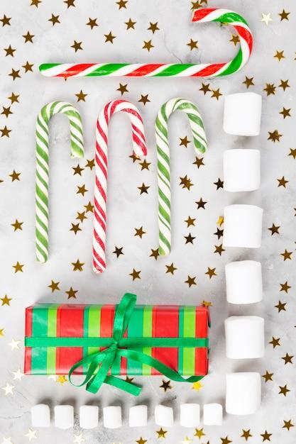 Рождественская геометрическая композиция. подарки, карамельные трости, зефир на сером фоне бетона с сверкающими звездами. Premium Фотографии