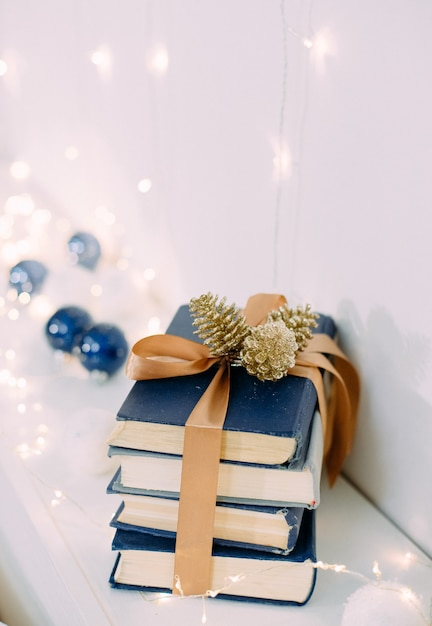 Christmas gift books with ribbons and garlands magic Premium Photo