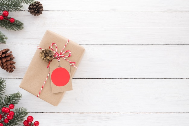christmas gift box and decorative elements on white wooden background premium photo