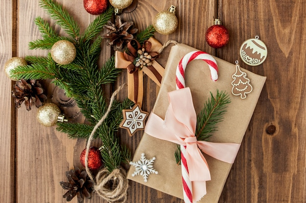 Christmas gift box, decor and fir tree branch on wooden table. top view with copyspace Premium Photo