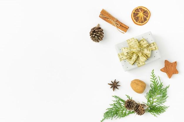 크리스마스 선물 상자 황금 리본 활 소나무 콘 주니퍼 너트 계피 프리미엄 사진