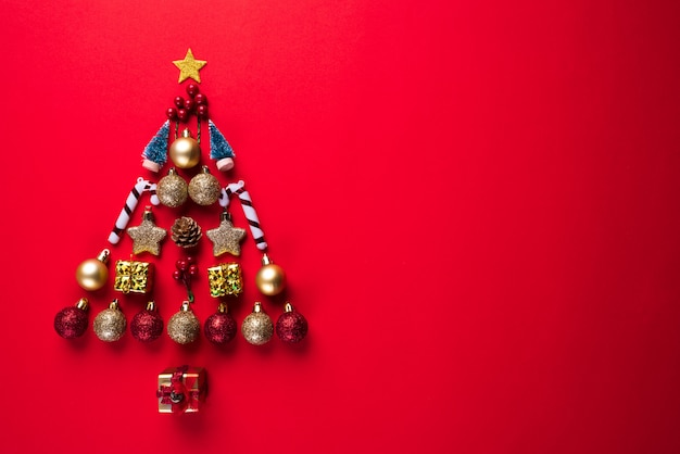 Christmas gift box, red ball and bell in shape of christmas tree, red background. Premium Photo
