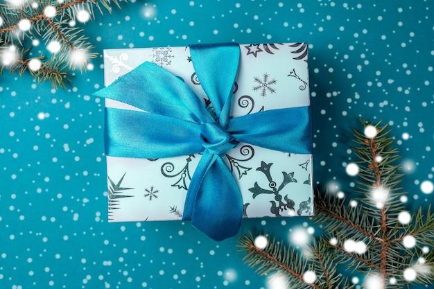 Рождественская подарочная коробка с бантом diy и еловыми ветками с нарисованным снегом на бирюзе. Premium Фотографии
