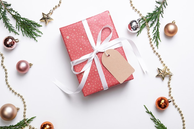 Premium Photo Christmas Gift Box With Paper Tag And Christmas Decorations On White Background Winter New Year Concept Flat Lay Top View Copy Space