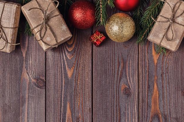クリスマスのギフトボックスと木製の背景にモミの木 Premium写真