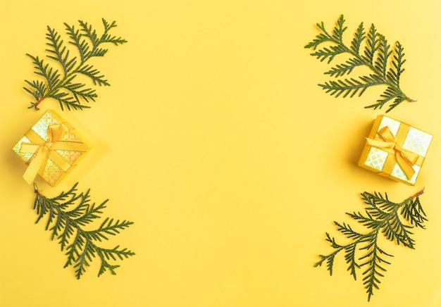 Рождественские подарочные коробки и зеленые ветви на желтом фоне. вид сверху. Premium Фотографии
