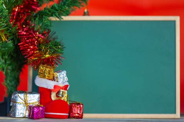 Christmas gift boxes in various colors placed in front of the green chalkboard Free Photo