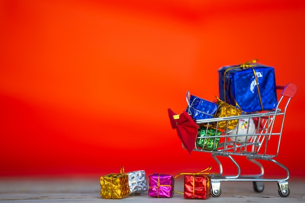 Christmas gift boxes in various colors placed in a shopping cart Free Photo