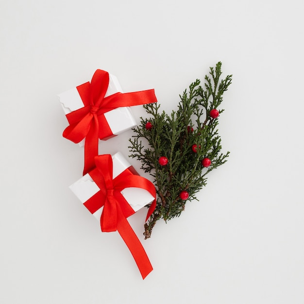 Christmas gift boxes with a mistletoe leave Free Photo