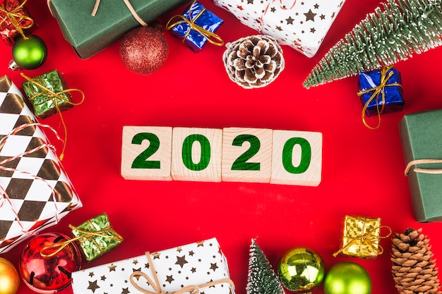 Christmas gift boxes with year 2020 on wooden blocks, preparation for holidays. top view Premium Photo